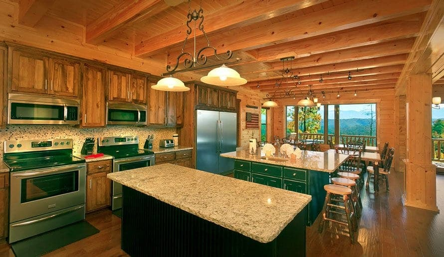 An oversized kitchen in a Pigeon Forge cabin featuring two stoves and two microwaves