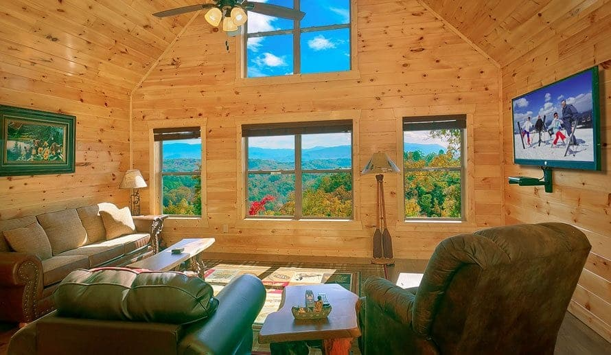 The living room of a Smoky Mountain cabin with plush furniture and scenic views
