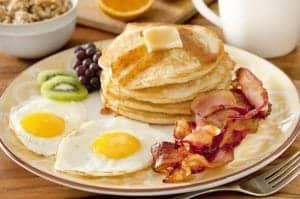 A plate of delicious pancakes, eggs, bacon, and fruit.