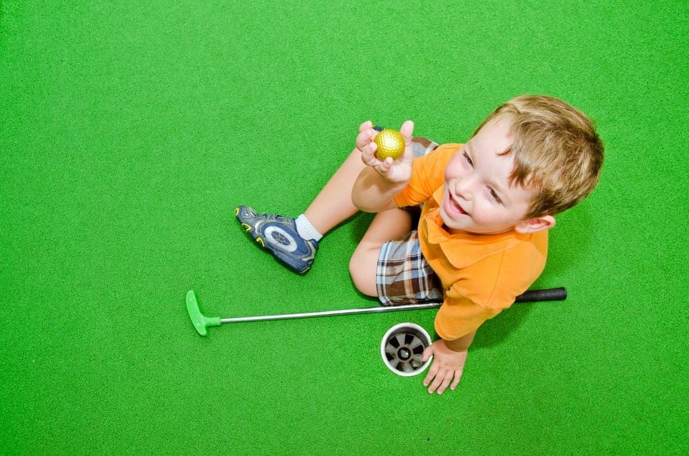 Young boy showing off golf ball after pulling it out of hole while playing miniature golf