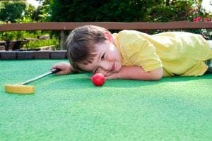 young boy plays miniature golf lines up golf ball